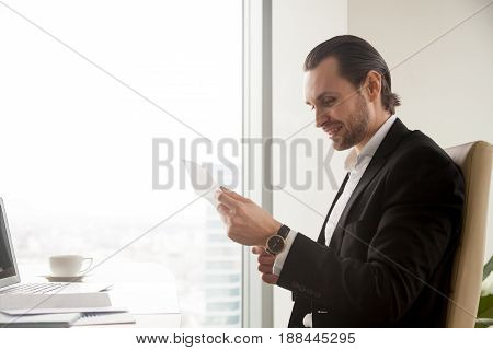 Happy businessman reading document at desk in office. Young guy entrepreneur examines notice, reading letter with good news. Manager satisfied with conditions of contract, receives bank loan approving