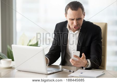 Businessman angry because of ill-timed or annoying phone call in time his working on laptop at office. Entrepreneur annoyed with cellphone breakdown or mobile app critical error, bad news in message