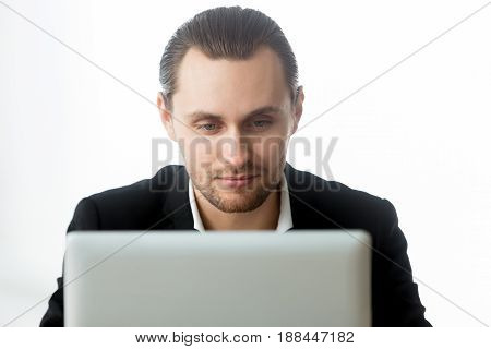 Young man working on laptop, communicates in social network, searching work in Internet. Male office worker write blog post, reading news on computer, browsing online. Ecommerce entrepreneur, close up