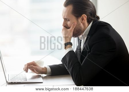 Businessman yawning while working on computer at workplace. Male entrepreneur suffering from lack of sleep, chronic fatigue and drowsiness at desk with laptop. Boring routine, monotonous office work