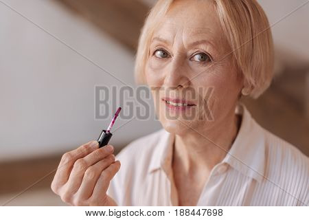 Love cosmetics. Beautiful female person wrinkling her forehead and keeping smile on face while looking straight at camera
