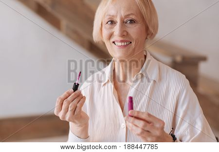 White teeth. Positive delighted woman holding bottle with lip-gloss in left hand standing in her room while expressing positivity