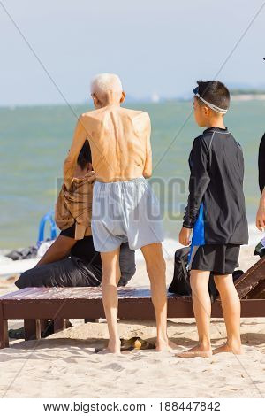 PHETCHABURI THAILAND - APRIL 7 : unidentified asian old man standing on the beach with his family on April 7 2017 in Phetchaburi Thailand.