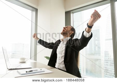 Happy businessman raises hands, screaming, ecstatic guy feels joy at desk in front of pc laptop. Positive entrepreneur celebrating victory with open arms. Impressive win, success, business great luck