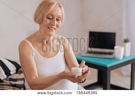 I am ready. Attractive woman keeping smile on her face looking downwards while touching her skin care cream