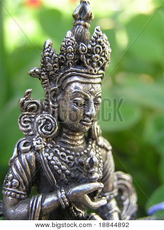 close up shot of a green tara statue in the garden