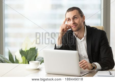 Young businessman dreaming about successful future at office desk. Attractive entrepreneur ponders decision, imagines positive result while working on laptop at workplace. Business inspiration concept