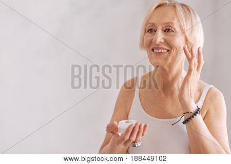 Face massage. Positive delighted blonde female holding bottle with cream keeping smile on face while raising left hand up