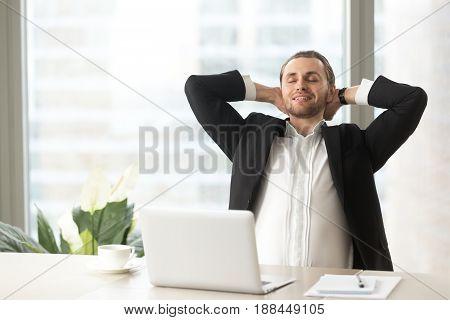 Satisfied businessman sitting at desk in front of laptop with closed eyes and hands behind head. Entrepreneur dreaming about future, enjoys short break at work. Office worker relaxing at workplace