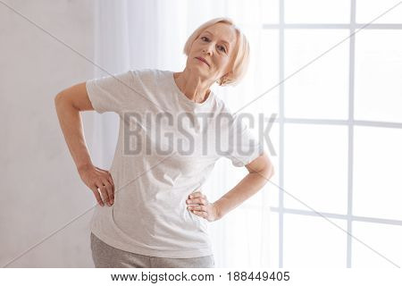 Be in good shape. Serious mature woman bent her back putting both hands on the belt while looking straight at camera