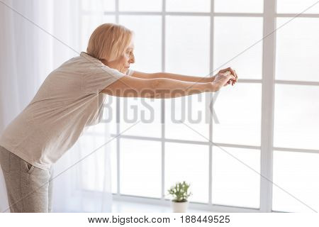 Do exercises. Serious senior female person bent her back standing in semi position while looking forward at her hands