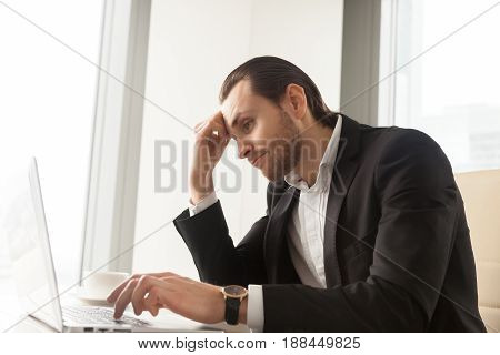 Young businessman at desk tired from routine laptop work. Entrepreneur boring at workplace, sick of monotonous work. Office worker procrastinates while trying complete dull report. Lack of motivation