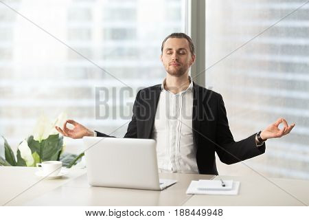 Relaxed corporate man sitting with closed eyes contemplating at work desk with laptop in office. Guy relaxing, relieves stress, gets positive thinking with yoga exercise. Stress free workplace concept