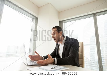 Businessman at work desk looking on laptop screen with surprise. Man in office shocked with unique low price offer, sale or huge discount in online shop. Young entrepreneur amazed with unexpected news