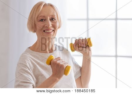 Be in good shape. Happy smiling woman wearing sport clothes and lifting dumbbells while looking straight on camera