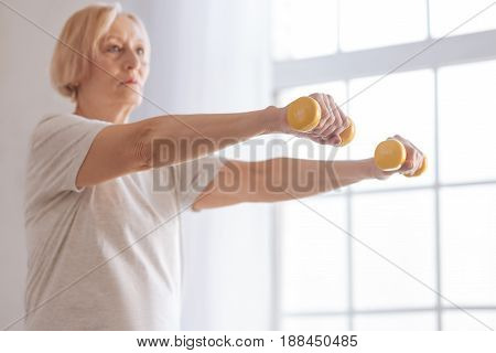 Be serious. Concentrated female standing in semi position pressing her lips while lifting dumbbells
