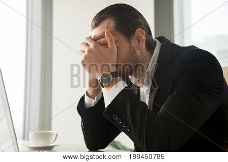 Frustrated businessman covering his face with hands while sitting at desk. Overworked entrepreneur tired of too much hard work, upset with company bankruptcy, suffering from stress and nervous tension