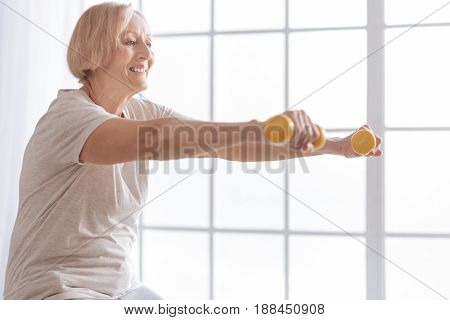 Do it slowly. Positive delighted pensioner keeping smile on her face while looking forward and taking care of her health