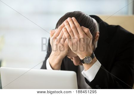 Businessman sitting head in hands shocked because of company bankruptcy, market crash, loss of savings. Young man in despair after receiving dismissal notice, confiscation of property through debt