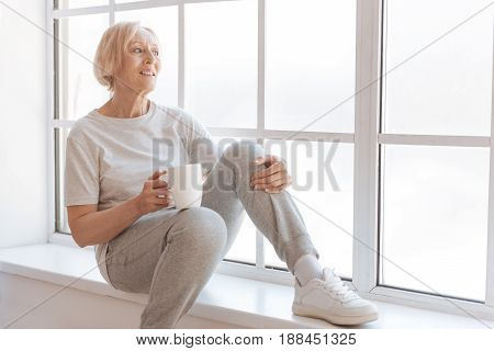 Have minute of relax. Enigmatical sportswoman sitting on the windowsill keeping white cup in right hand while putting left hand on left knee