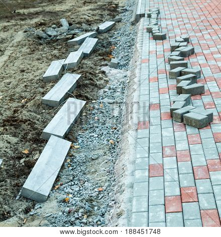 Paving the footpath with gray and red tiled cubes. Unset concrete border (curb-stone) at the edge of the path.