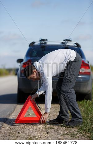 Photo of young brunette putting red triangle on road near broken car in afternoon