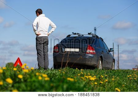 Photo of man near broken car on road during day