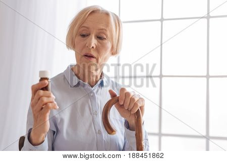Read attentively. Confident retirement keeping mouth opened leaning on walking stick while holding medicine in right hand