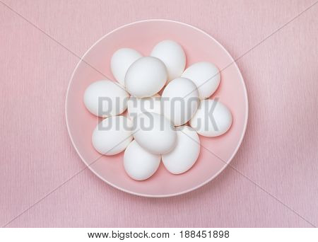 Top view of a dozen of white eggs on the pink plate and pink background, isolated. Design, visual art, minimalism, concept.