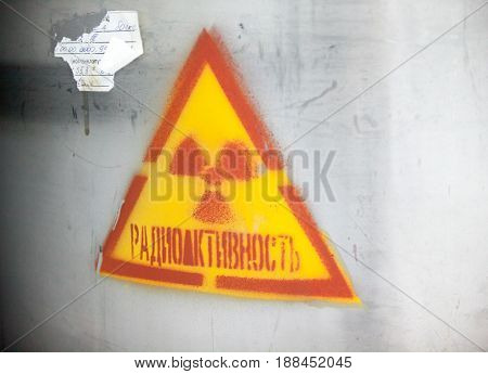 CHERNOBYL UKRAINE - OCTOBER 16 2015: Ionizing radiation trefoil symbol painted on the gray metal surface at Chernobyl Nuclear Power Plant. Radioactivity sign. Inscription in Russian.