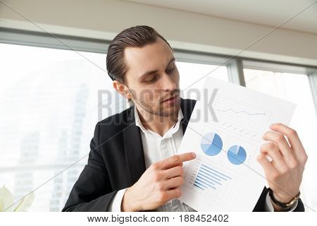Financial director makes video conference call presentation, talks about company success, research results, analyzes statistic data. Businessman holds document with graphs, charts, curves fluctuations