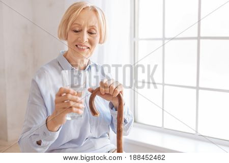 Just look here. Smiling female person holding glass in right hand putting left hand on the cane while expressing positivity