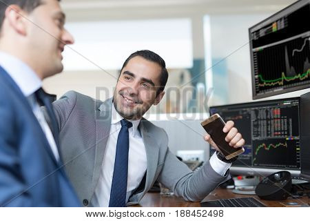 Successful businessmen trading online. Stock traders looking at graphs, indexes and numbers on multiple computer screens. Colleagues in traders office. Business success.