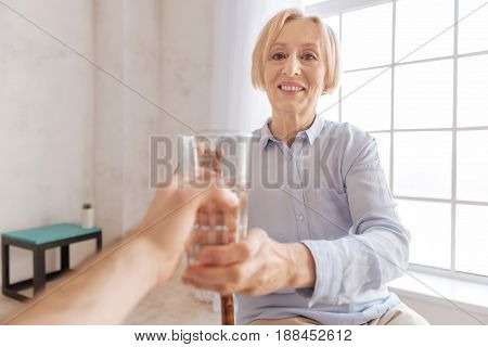 I need it. Positive retirement woman taking glass with water sitting opposite male person while looking at him