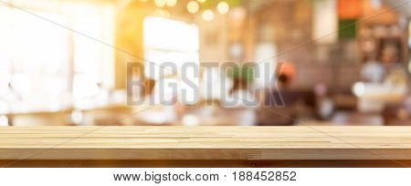 Wood table top on blur coffee shop (cafe) interior background panoramic banner - can be used for display your products or foods