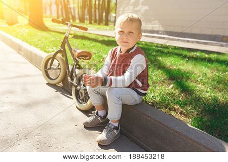 Photo of boy sitting on curb at park in run bicycle background