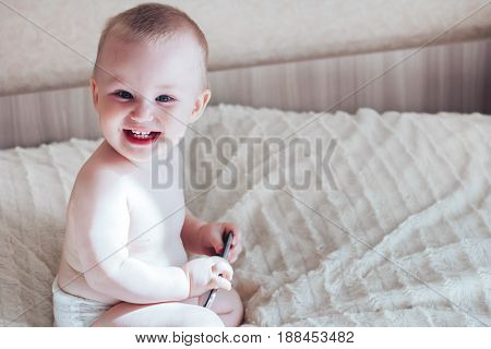 baby boy play with mobile phone and laughing