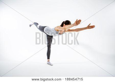 Girl balances on one leg at isolated background