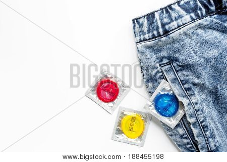 condoms and jeans for male contraception and birth control on white background top view mockup