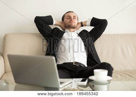 Man in business suit slumbers on sofa, hands behind head, of laptop on coffee table. Businessman with closed eyes enjoys rest after completing important work. Entrepreneur relaxing on break in office