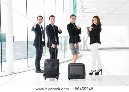 Group of business people with luggage giving thumbs up in building hallway (airport terminal) - business travel concept