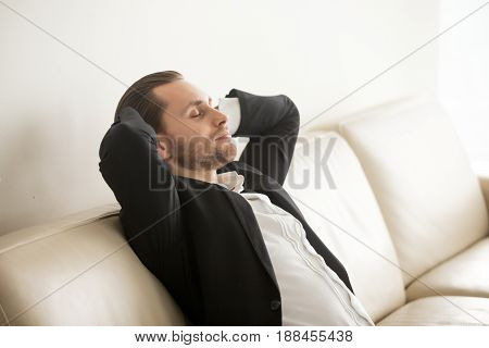 Successful businessman dozing on comfortable sofa with hands behind head. Entrepreneur resting on home coach after work day. Dreamy young man imagines positive future, relaxing during break in office