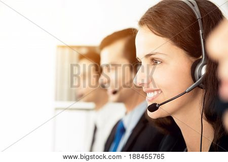 Smiling call center (or telemarketer) team working in the office