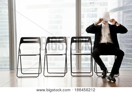 Office worker covering face with sheet of paper when boring while waiting for meeting in office reception. Job applicant, candidate on post tired, waits for an interview, worries before important talk