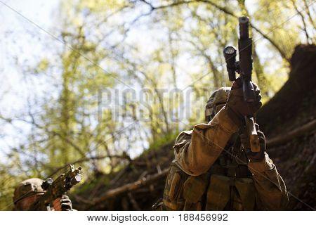 Soldier with gun in forest, photo below