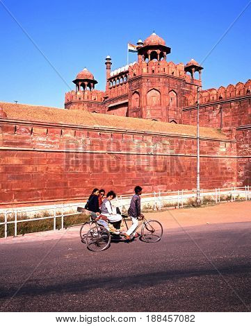 DELHI, INDIA - NOVEMBER 20, 1993 - View of the Red Fort with local people on a tricycle in the foreground Delhi Delhi Union Territory India, November 20, 1993.