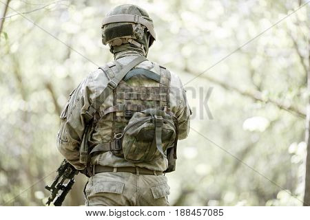 Photo from back of soldier with submachine-gun in woods during day
