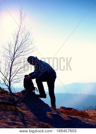 Professional Photographer Is Packing Camera Into Backpack On Peak Of Rock. Dreamy Fogy Landscape, Sp