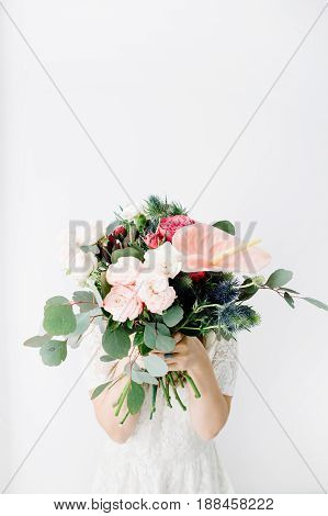Pretty woman with beautiful flowers bouquet: bombastic roses blue eringium anthurium flower eucalyptus branches at white wall. Front view. Floral lifestyle composition.