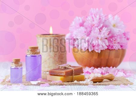 lavender oil, soap, salt, fresh flowers, candle, on pink for spa and wellness bokeh